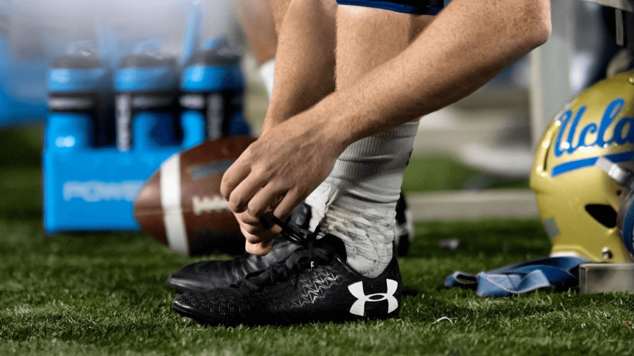 TUCSON, AZ - OCTOBER 14: A UCLA Bruins players adjusts his Under Armour cleats during the college football game between the UCLA Bruins and the Arizona Wildcats on October 14, 2017, at Arizona Stadium in Tucson, AZ. Arizona defeated UCLA 47-30. (Photo by Carlos Herrera/Icon Sportswire via Getty Images)
