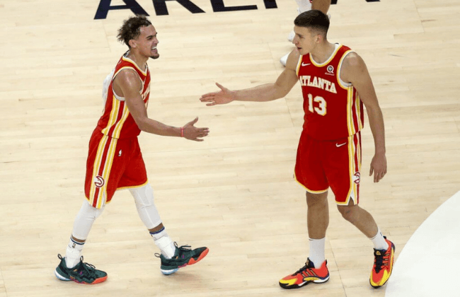 May 28, 2021; Atlanta, Georgia, USA; Atlanta Hawks guard Trae Young (11) and guard Bogdan Bogdanovic (13) celebrate against the New York Knicks in the fourth quarter during game three in the first round of the 2021 NBA Playoffs at State Farm Arena. Mandatory Credit: Brett Davis-USA TODAY Sports