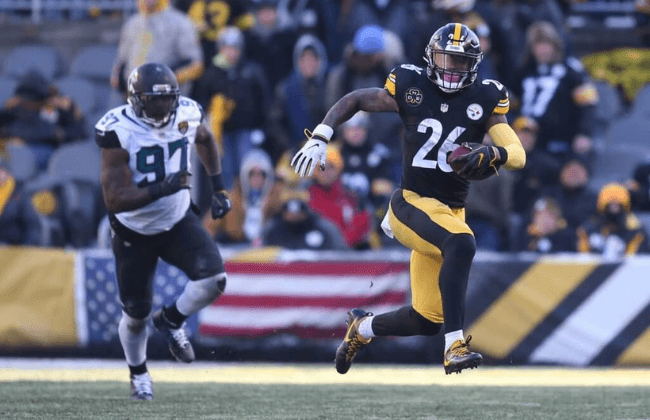 Jan 14, 2018; Pittsburgh, PA, USA; Pittsburgh Steelers running back Le'Veon Bell (26) carries the ball past Jacksonville Jaguars defensive tackle Malik Jackson (97) during the second half in the AFC Divisional Playoff game at Heinz Field. Mandatory Credit: Charles LeClaire-USA TODAY Sports
