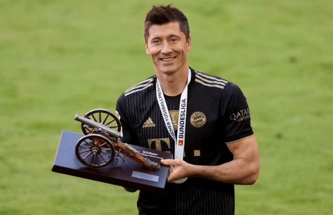MUNICH, GERMANY - MAY 22: Robert Lewandowski of FC Bayern Muenchen raises the top goalscorer of the season award following the Bundesliga match between FC Bayern Muenchen and FC Augsburg at Allianz Arena on May 22, 2021 in Munich, Germany. After the Bavarian cabinet decided on first relaxations for outdoor events, the current Corona situation allows FC Bayern to have its last match of the season in front of 250 spectators in the Allianz Arena. Of these, 100 tickets are given to people from the health sector selected by the Ministry of Health.