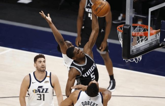 Apr 10, 2021; Salt Lake City, Utah, USA; Sacramento Kings guard De'Aaron Fox (5) dunks over Utah Jazz center Rudy Gobert (27) in the third quarter at Vivint Smart Home Arena. Mandatory Credit: Jeffrey Swinger-USA TODAY Sports
