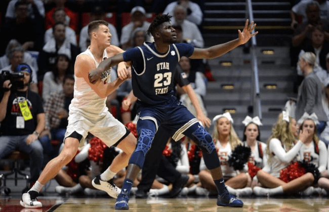 Feb 1, 2020; San Diego, California, USA; Utah State Aggies center Neemias Queta (23) and San Diego State Aztecs forward Yanni Wetzell (L) battle for position during the first half at Viejas Arena.