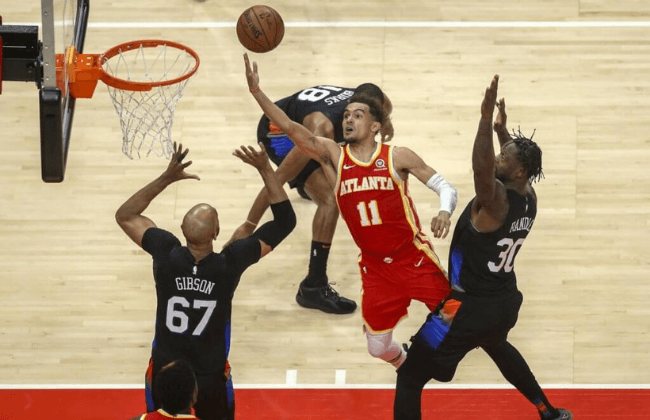 May 28, 2021; Atlanta, Georgia, USA; Atlanta Hawks guard Trae Young (11) shoots the ball past New York Knicks center Taj Gibson (67) and forward Julius Randle (30) in the second quarter during game three in the first round of the 2021 NBA Playoffs at State Farm Arena. Mandatory Credit: Brett Davis-USA TODAY Sports