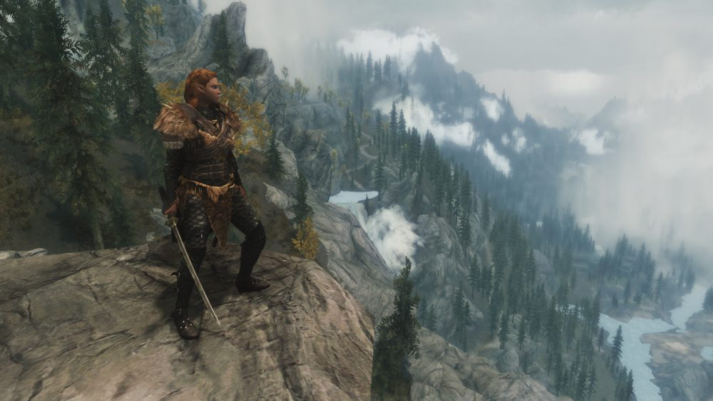 A Skyrim screenshot showing a character standing on a mountain. Skyrim, Bethesda, 2011.
