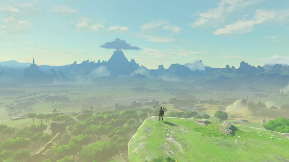 A screenshot of Breath of the Wild. Link stands on a cliff, gazing out at Hyrule.