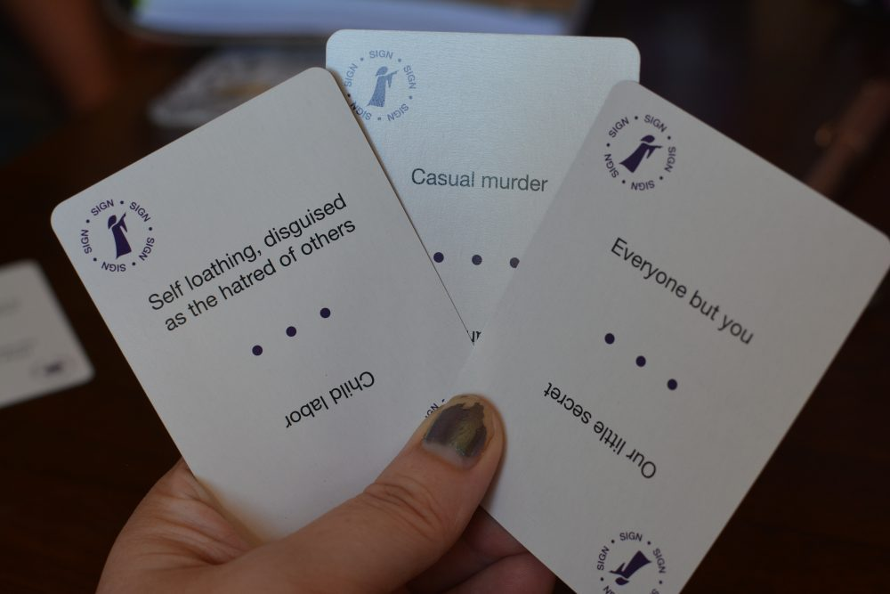"Melissa holds three Cult Following ""sign"" cards that list potential cult traits. Cult Following, Bravely Told Games, 2017."