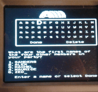 "A photograph of a handheld Oregon Trail game. The screen asks players to input party member names. Party members include: Sanders, Alex, Rachel, Maurice, and Zed. Yes, ""Zed"" is a reference to Zardoz, which we had watched the night before. The Oregon Trail, MECC, Brøderbund, 1971."