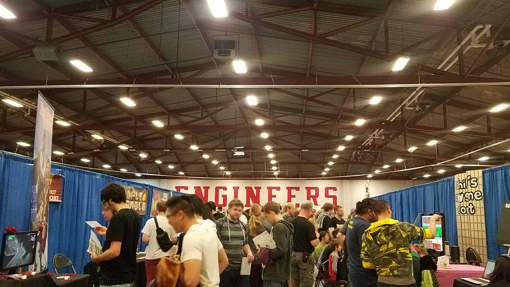 A crowd of people fill the center of an aisle as tables and displays of games adorn the side. the word ENGINEERS is on the farthest back wall.