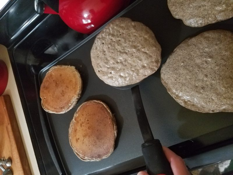 A photo of buckwheat pancakes cooking on a griddle.