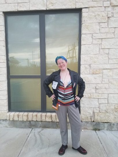 """Jamey dressed as Scooter Rex. They have blue hair, and are wearing a black leather jacket with a patch reading """"NAZI PUNKS FUCK OFF"""" over a multicolored shirt, gray pants, and brown shoes."""
