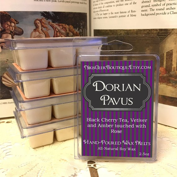 "An image of several wax melts. The package reads, ""NikisGeekBoutique.Etsy.com. Dorian Pavus. Black Cherry Tea, Vetiver and Amber touched with Rose. Hand-Poured Wax Melts. All-Natural Soy Wax."""