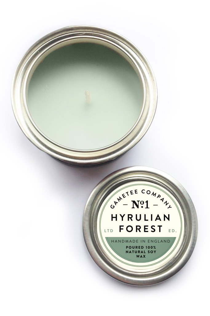 """A photo of a green candle. A label on the lid reads """"GameTee Company No. 1. Hyrulian Forest. Handmade in England. Poured 100% Natural Soy Wax."""""""
