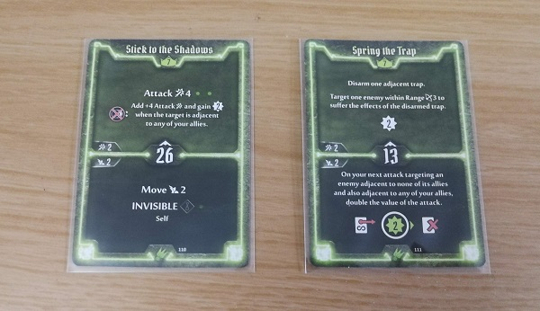 Two green cards, in sleeves, listing abilities Stick to the Shadows and Spring the Trap. Each contains a top and bottom half, with different actions shown. In the middle is a number that determines initiative.