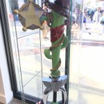"A keyblade with the blade made out of a green cactus wrapped in a rope and a bandana, wearing a brown wide-brimmed hat. A badge reading ""Sheriff"" is attached to the blade. The handle has the shape of a rocketship with Buzz Lightyear's white and blue motif. The keyblade sits in a glass case at Disney Springs. Kingdom Hearts Pop-Up, Disney Springs, 2018"