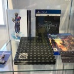 A glass display case at Disney Springs containing a copy of the Kingdom Hearts 3 Deluxe edition, the steel book case with a dark gray plaid pattern on it, a collectible pin depicting the title of the game and Sora with a crown on his head, and an artbook showing Sora standing in clear water, a yellow paopu fruit in his hand. Kingdom Hearts Pop-Up, Disney Springs, 2018