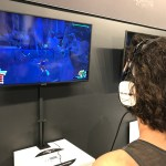 A young man with short curly hair stands in front of a tv playing the Kingdom Hearts 3 demo on the PlayStation 4. On the screen, Sora, the protagonist for Kingdom Hearts, scales a cliff wall in an effort to avoid the rock Titan boss fight monster in the Colosseum world. Kingdom Hearts Pop-Up, Disney Springs, 2018