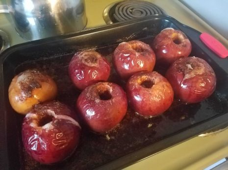 A photo of eight cooked hot buttered apples.