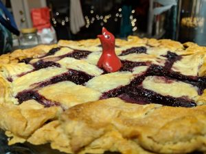 A photo of a beautiful, crispy, juicy blackberry pie with a red pie bird sitting in the middle. Blurry lights in the background add to the image to create a happy mood.