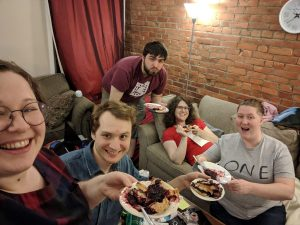 Photo of five people including the author of this piece and Sidequest contributor E. Forney, eating the blackberry pie and looking very pleased with themselves.