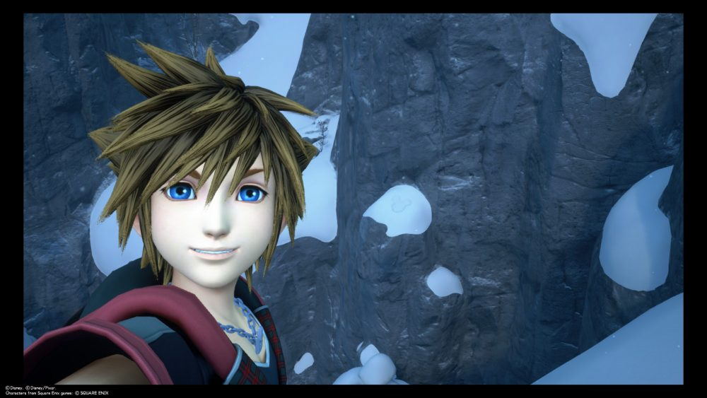 Sora takes a selfie in the snowy mountains of Arendelle. A Lucky Emblem is imprinted into the snow to the right of his head. Kingdom Hearts III, Square Enix, 2019