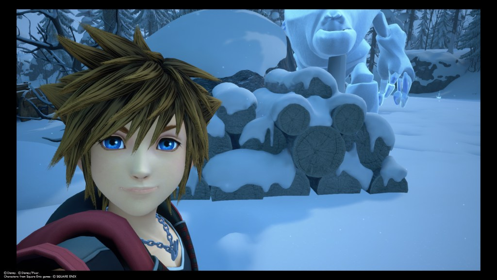Sora takes a selfie in front of a pile of logs shaped like a Lucky Emblem in Arendelle. Kingdom Hearts III, Square Enix, 2019.
