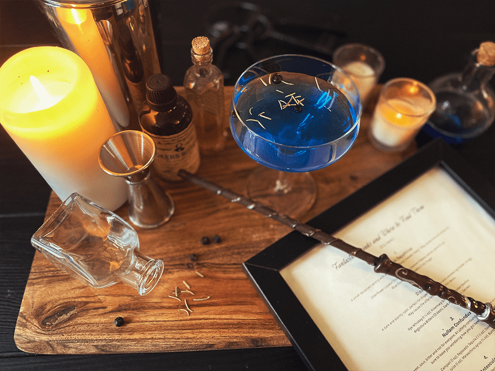 A collection of drink mixing equipment, a cocktail, and a menu of Fantastic Drinks themed cocktail recipes.