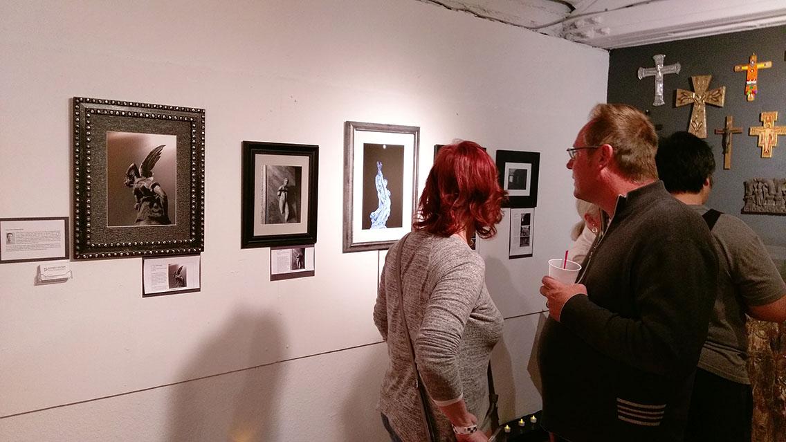 Guests looking at photographs at art exhibit