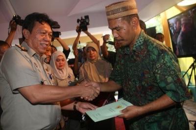Kepala BPN Sidoarjo, Nandang Agus Taruna saat menyerahkan sertifikat tanah milik warga Desa Kupang