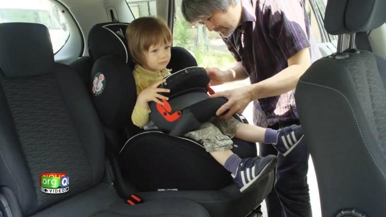 Un enfant est en train de s'installer dans son siège auto avec bouclier d'impact