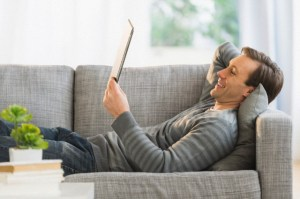 Man lying on sofa watching tablet pc