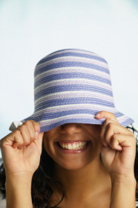 Close up of woman smiling while pulling hat down over her eyes