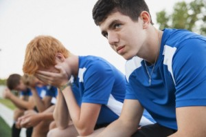 Soccer players looking disappointed on bench.