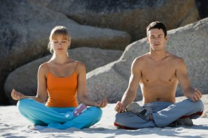 Couple meditating on beach