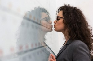 Businesswoman kissing her reflection on wall