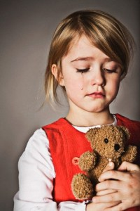 Girl holding teddy bear and crying --- Image by © Tomas Rodriguez/Corbis