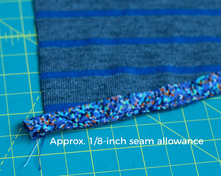 I used a one-eighth-inch seam allowance to finish my knit T-shirt hem with woven bias tape.