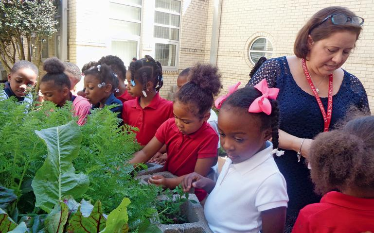 A teacher and students in the garden at L.S. Rugg Elementary School in Alexandria, Louisiana.