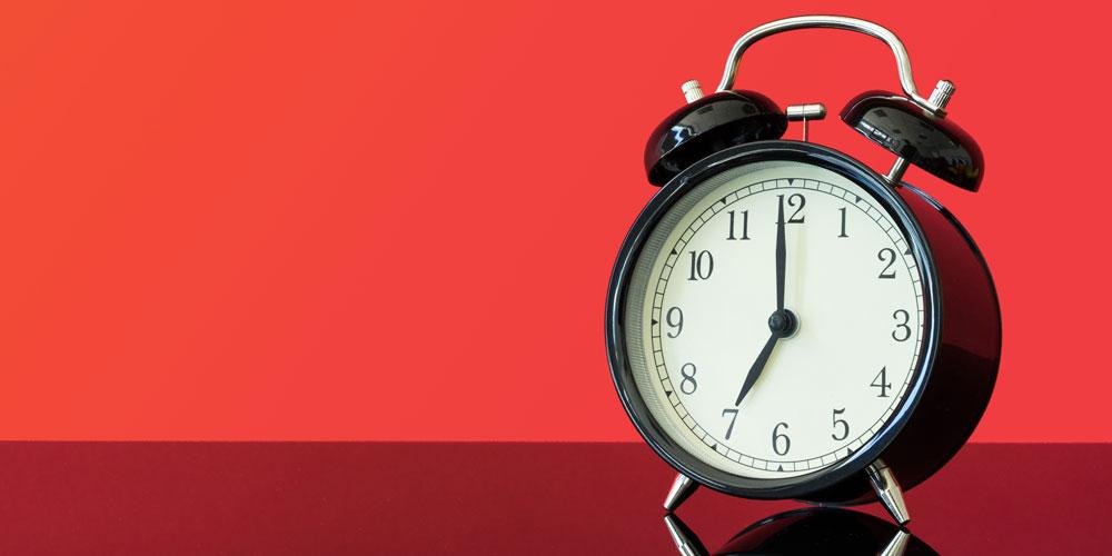 Vintage alarm clock on red background