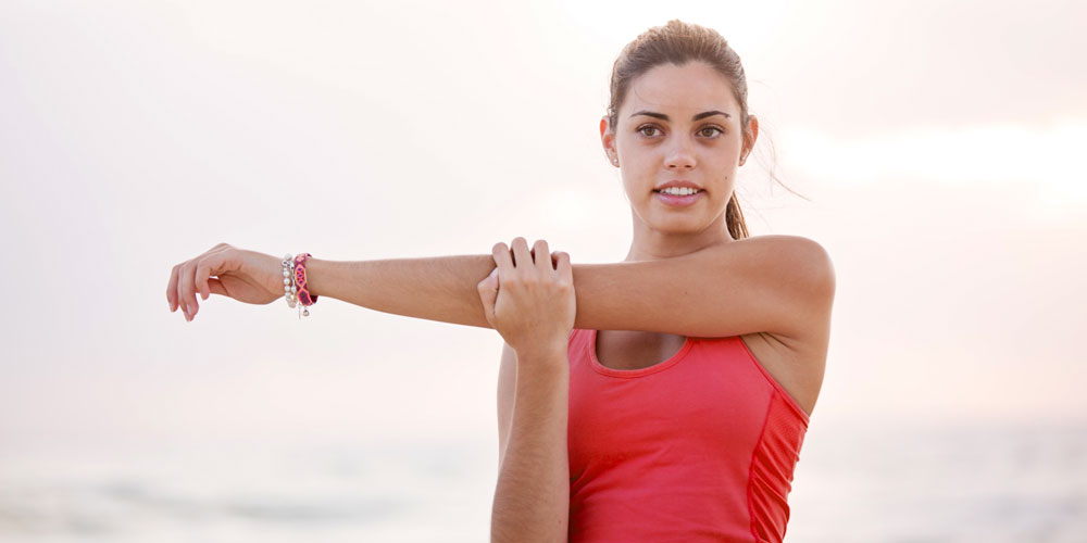 Young athlete stretching her arms