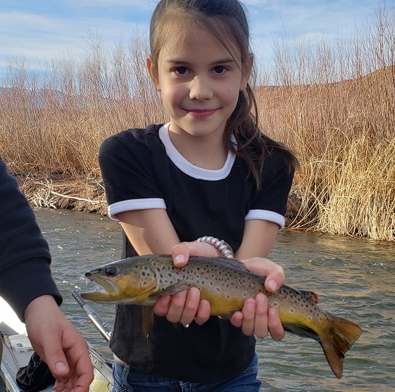 Young girl holds a beautiful brown above the water