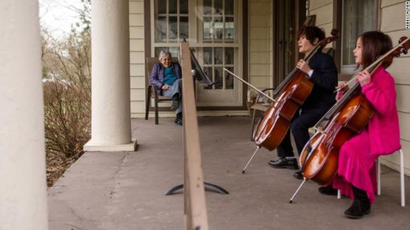 Two kids play music for an elderly neighbour to entertain her in lock-down period