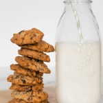 Cookies stacked in a pile next to a glass container with milk.