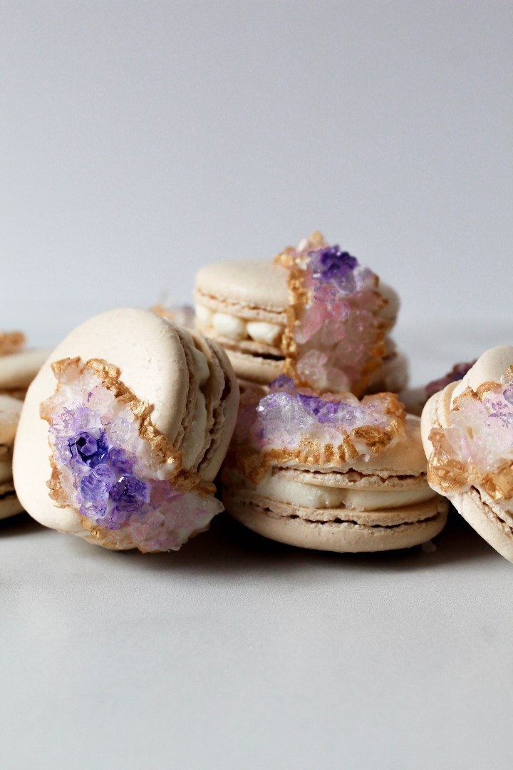 Geode Macarons laying on top of each other on a white surface