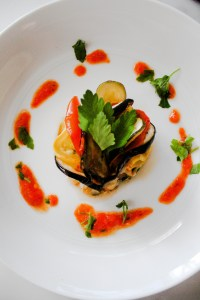 Ratatouille on a white plate surrounded by sauce and parsley.