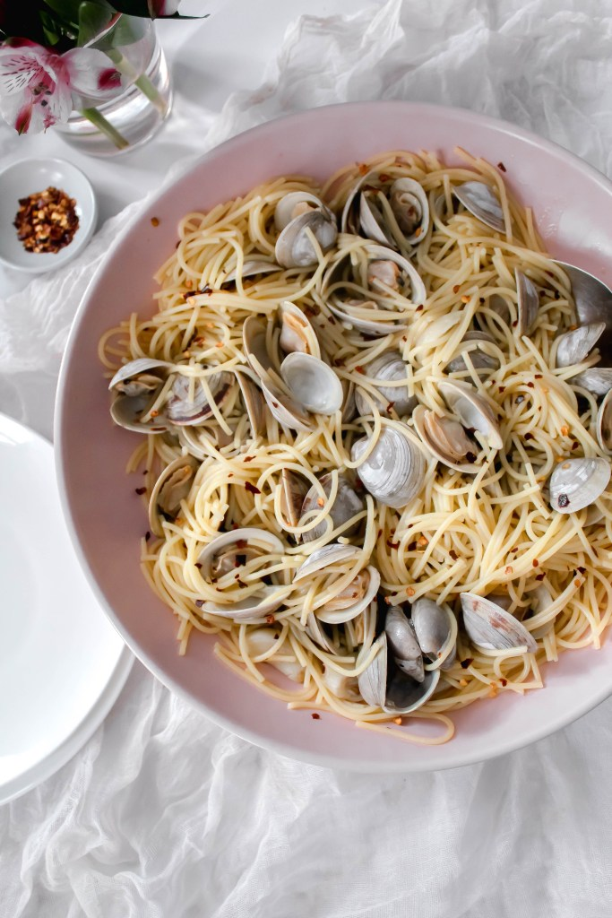 Linguine and clams with red pepper flakes sitting in a pink serving bowl.