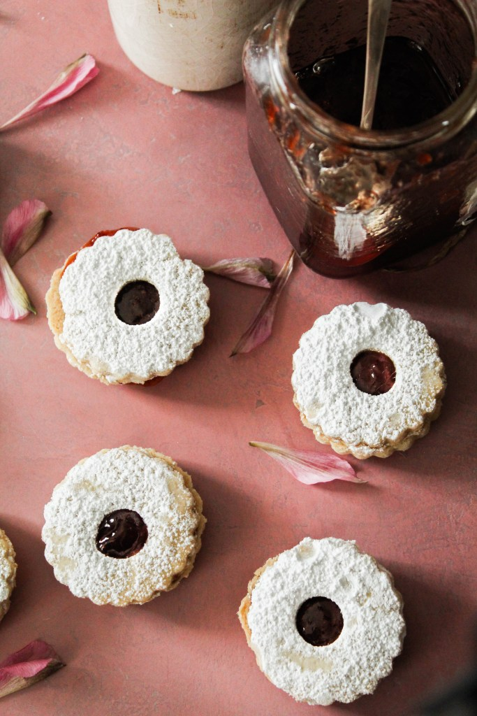 Four linzer cookies on a pink background with jam and flower petals.