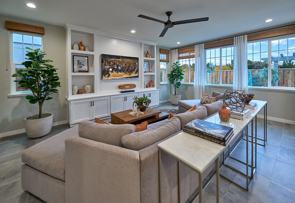 great room with tan sectional sofa, sofa table with metal legs, wooden coffee table, white entertainment center, several windows