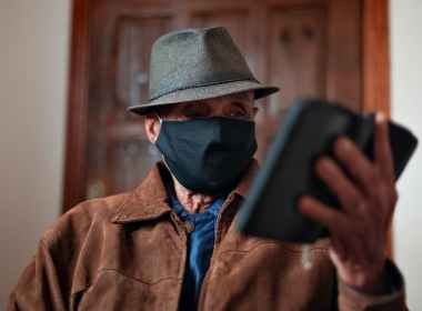 aged man in protective mask with smartphone