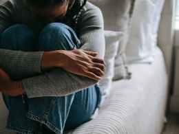 crop pitiful black woman embracing knees on bed
