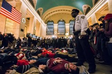 A police officer stands over activists, demanding justice for the death of Eric Garner, as they stage a 'die in' during rush hour at Grand Central Terminal in the Manhattan borough of New York on December 3, 2014. REUTERS/Adrees Latif
